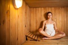 Mujer que se relaja en una sauna Imágenes de archivo libres de regalías