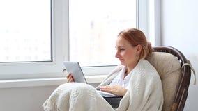 Mujer que se relaja en una silla de mimbre blanca en su sala de estar que trabaja en un ordenador portátil metrajes