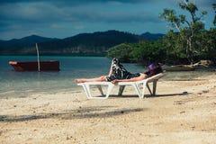 Mujer que se relaja encendido sunbed en las zonas tropicales Fotografía de archivo
