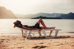 Mujer que se relaja encendido sunbed en las zonas tropicales Fotos de archivo libres de regalías