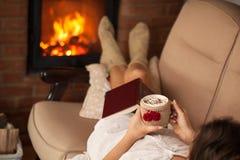 Mujer que se relaja por el fuego que sostiene una taza de chocolate caliente con c Imagenes de archivo