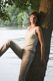 Mujer que se relaja por el lago Imagen de archivo libre de regalías