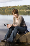 Mujer que se relaja por el lago o el mar Fotos de archivo libres de regalías