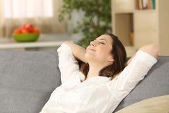 Mujer que se relaja solamente en un sofá en casa imagenes de archivo
