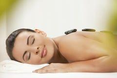 Mujer que se relaja teniendo masaje de piedra caliente del tratamiento Imagen de archivo libre de regalías