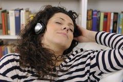 Mujer que se relaja y que escucha la música Foto de archivo