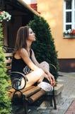 Mujer que se relaja y que se sienta en banco Imagenes de archivo