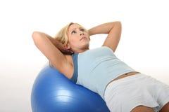Mujer que se resuelve con la bola del ejercicio Foto de archivo libre de regalías