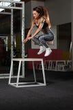 Mujer que se resuelve con la caja del ajuste en el gimnasio Fotografía de archivo