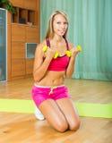 Mujer que se resuelve con pesas de gimnasia Foto de archivo libre de regalías