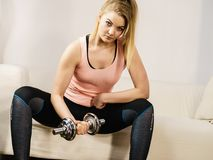 Mujer que se resuelve en casa con pesa de gimnasia Foto de archivo