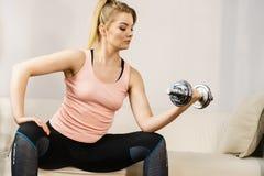 Mujer que se resuelve en casa con pesa de gimnasia Imagenes de archivo