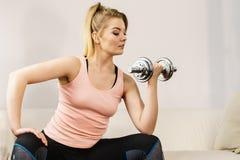 Mujer que se resuelve en casa con pesa de gimnasia Foto de archivo libre de regalías