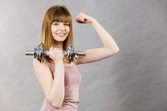 Mujer que se resuelve en casa con pesa de gimnasia Fotografía de archivo libre de regalías