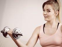 Mujer que se resuelve en casa con pesa de gimnasia Fotos de archivo libres de regalías