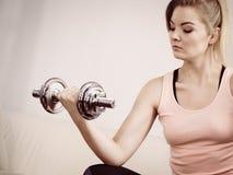 Mujer que se resuelve en casa con pesa de gimnasia Imagen de archivo libre de regalías