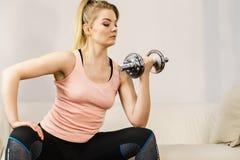 Mujer que se resuelve en casa con pesa de gimnasia Imagen de archivo