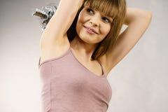 Mujer que se resuelve en casa con pesa de gimnasia Fotos de archivo