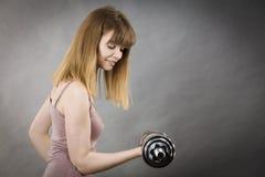Mujer que se resuelve en casa con pesa de gimnasia Imágenes de archivo libres de regalías
