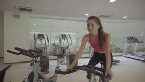 Mujer que se resuelve en la bicicleta estática en el gimnasio Ejercicio femenino en la bicicleta almacen de metraje de vídeo