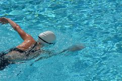 Mujer que se resuelve en una piscina de la propiedad horizontal Foto de archivo libre de regalías