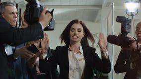 Mujer que se rompe a través de periodistas después de conferencia