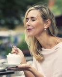 Mujer que se sienta afuera en el café y el café de consumición Imagen de archivo libre de regalías