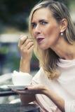 Mujer que se sienta afuera en el café y el café de consumición Imágenes de archivo libres de regalías