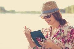 Mujer que se sienta al aire libre y que lee un libro Fotos de archivo libres de regalías
