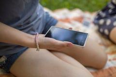 Mujer que se sienta al aire libre y que sostiene un smartphone Imágenes de archivo libres de regalías