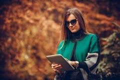 Mujer que se sienta al aire libre y que usa una tableta Imagen de archivo libre de regalías