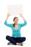 Mujer que se sienta al lado de tarjeta en blanco Imágenes de archivo libres de regalías