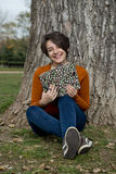 Mujer que se sienta al lado de un árbol, celebrando un libro y una sonrisa Foto de archivo