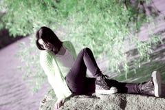 Mujer que se sienta al lado de un río Imagen de archivo