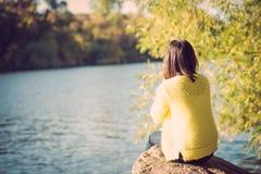 Mujer que se sienta al lado de un río Fotos de archivo libres de regalías