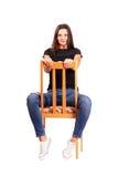 Mujer que se sienta al revés en la silla que presenta mirando la cámara Imagen de archivo