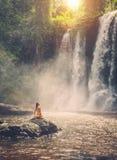 Mujer que se sienta cerca de la cascada que goza del sol, Phnom Koulen en Siem Reap, Camboya Imágenes de archivo libres de regalías