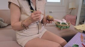 Mujer que se sienta cerca de la tabla y que pinta en el huevo de Pascua