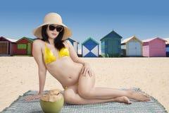 Mujer que se sienta cerca de las chozas de la playa Imagen de archivo libre de regalías