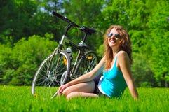 Mujer que se sienta cerca de su bici Imágenes de archivo libres de regalías