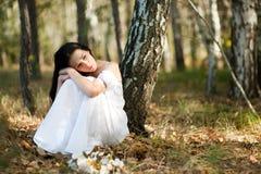 Mujer que se sienta cerca del árbol foto de archivo libre de regalías