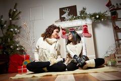 Mujer que se sienta cerca del árbol de navidad con su hija fotografía de archivo