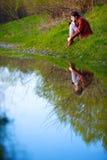 Mujer que se sienta cerca del agua, Foto de archivo libre de regalías