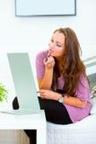 Mujer que se sienta cerca del espejo y que aplica el lápiz labial Foto de archivo