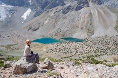 Mujer que se sienta cerca del lago en las montañas Fotografía de archivo