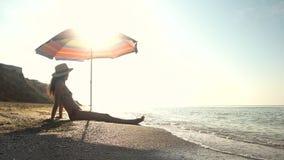 Mujer que se sienta cerca del parasol de playa almacen de metraje de vídeo