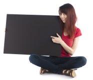 Mujer que se sienta con cartulina negra con el espacio del texto Imagen de archivo libre de regalías