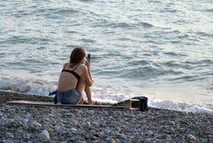 Mujer que se sienta con cellphone Fotos de archivo libres de regalías