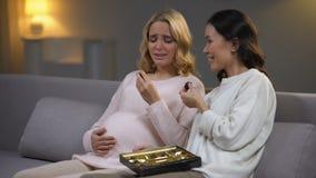 Mujer que se sienta con el amigo embarazada trastornado, comiendo los caramelos de chocolate, hormonas almacen de metraje de vídeo