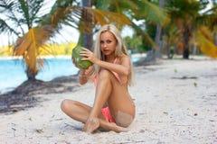 Mujer que se sienta con el coco en la playa blanca de la arena Imagen de archivo